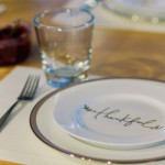 holiday table place setting with thankful written on plate - grieving through the holidays