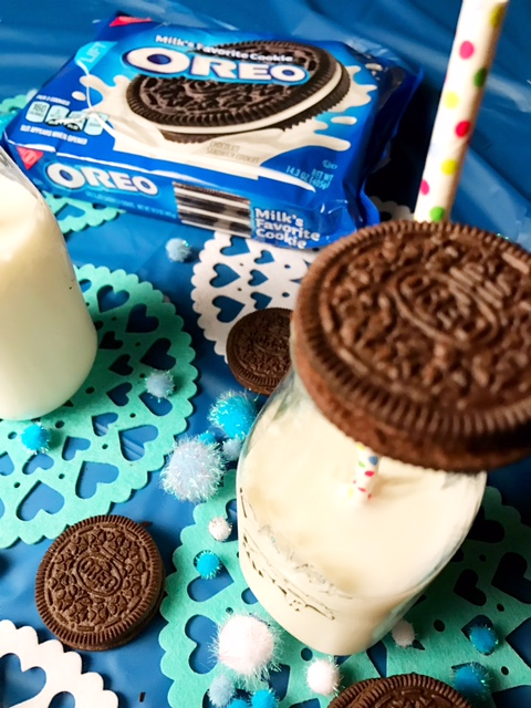 glass of milk with straw and cookie - oreo dunk challenge