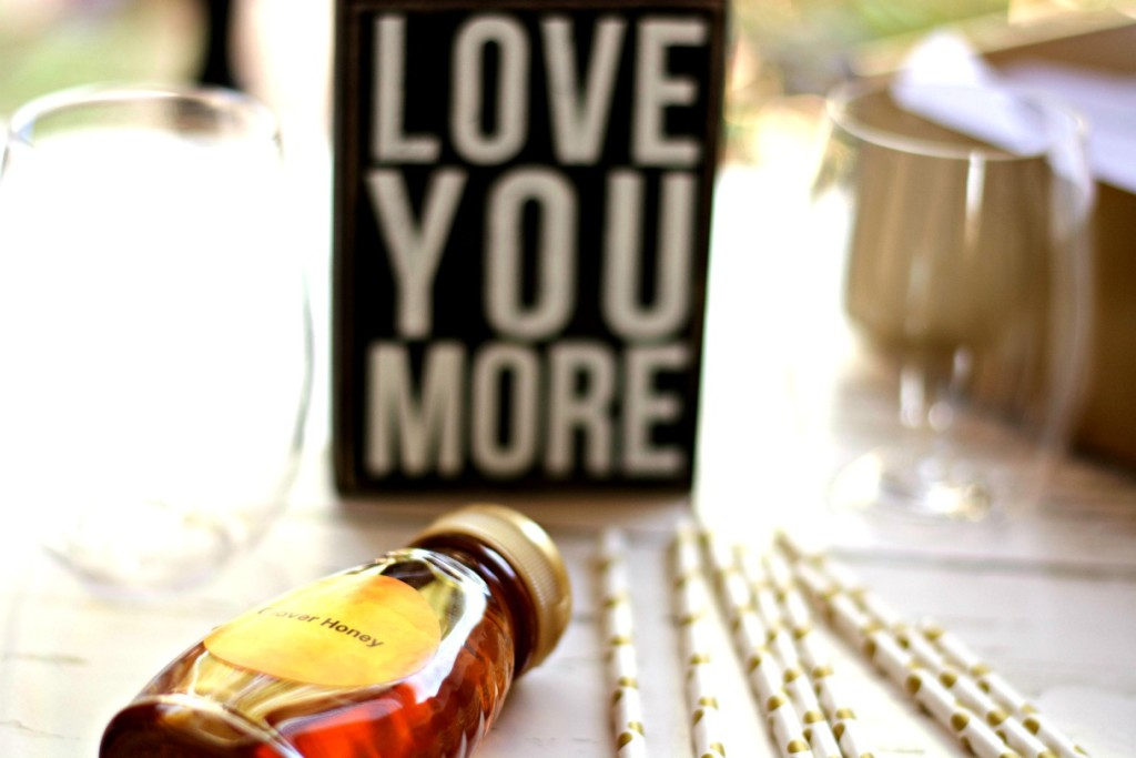 love you more wooden sign on white wooden table - planning date nights